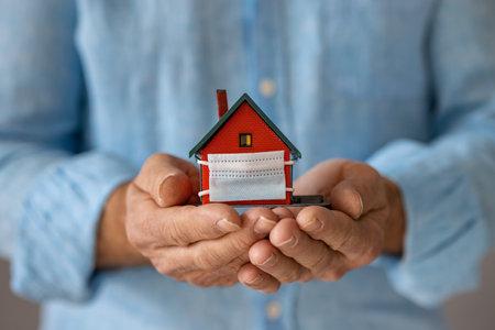 Senior businessman holding model house wearing protective medical mask in hands Foto de archivo