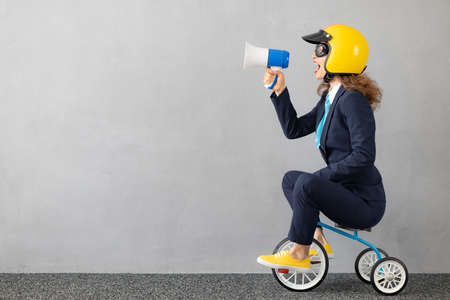 Successfull businesswoman driving toy car outdoor. Funny young woman shouting through megaphone against concrete wall background. Business srart up and winner concept