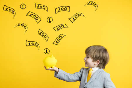 Happy child holding piggy bank against yellow background. Business start up and education concept