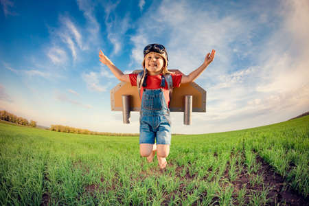 Happy child jumping against blue sky. Kid having fun in spring green field outdoor. Portrait of boy with paper wings. Freedom and imagination concept Foto de archivo