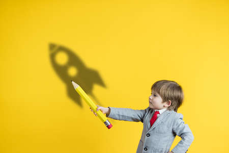 Happy child holding pencil against yellow background. Business start up and education concept