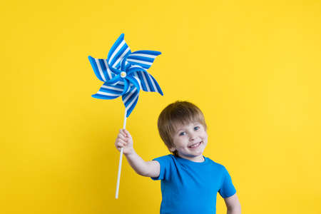 Child holding toy wind turbine against yellow background