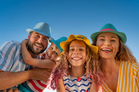Happy family having fun against blue sky background. Mother, father, daughter and son on summer vacation Foto de archivo