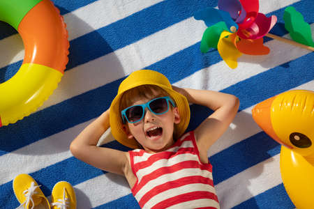 Happy child lying on striped towel outdoor. Top view portrait of kid. Funny baby smiling. Summer vacation concept Foto de archivo