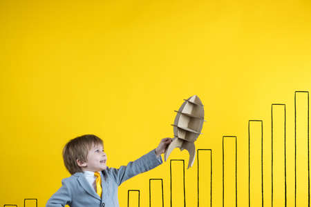 Happy child holding paper rocket against yellow background. Business start up and education concept Foto de archivo