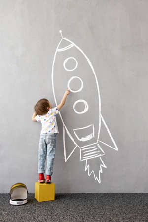Dream big! Happy kid draws a chalk rocket on the wall. Children imagination concept