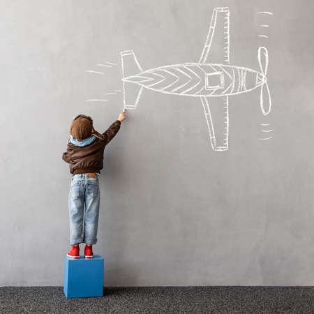 Dream big! Happy kid draws a chalk airplane on the wall. Children imagination and travel concept 스톡 콘텐츠