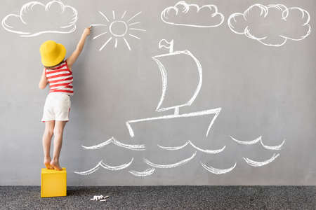 Dream big! Happy kid draws a chalk ship on the wall. Children imagination and summer vacation concept 스톡 콘텐츠
