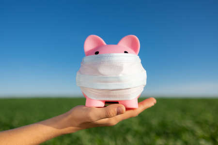 Piggybank wearing protective mask in hand against spring green field