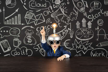 Bright idea! Funny child student in class against black chalkboard. Happy kid pretend to be businessman. Online education and e-learning concept. Back to school