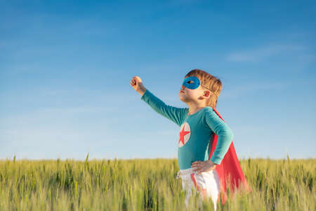 Superhero child playing outdoor in green field. Portrait of super hero kid against summer blue sky background. Freedom and children's dream concept 스톡 콘텐츠