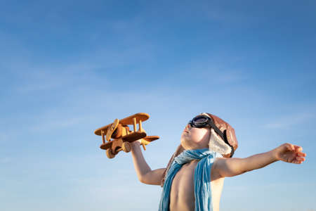 Happy child with wooden airplane playing outdoor in summer. Portrait of kid against summer blue sky background. Freedom and children's dream concept