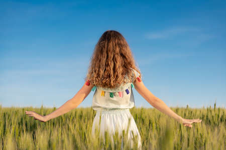 Happy child enjoying the sun outdoor in green field. Portrait of beautiful girl against summer blue sky background
