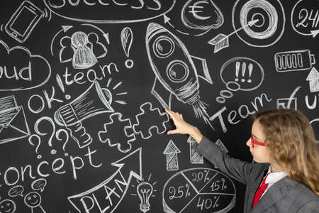 Young businesswoman against chalkboard with business sketch. Success marketing plan and startup concept