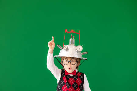 Bright idea! Funny child student in class. Happy kid against green chalkboard. Online education and e-learning concept. Back to school. Education, start up and business idea concept