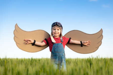 Happy child with cardboard wings playing outdoor in green field. Portrait of kid against summer blue sky background. Freedom and children's dream concept