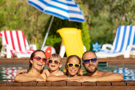 Happy family having fun on summer vacation. Father, mother and children playing in swimming pool. Active healthy lifestyle concept 스톡 콘텐츠