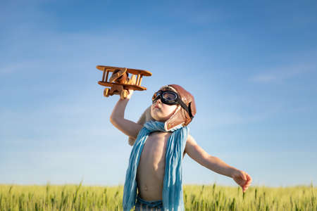 Happy child with wooden airplane playing outdoor in green field. Portrait of kid against summer blue sky background. Freedom and children's dream concept