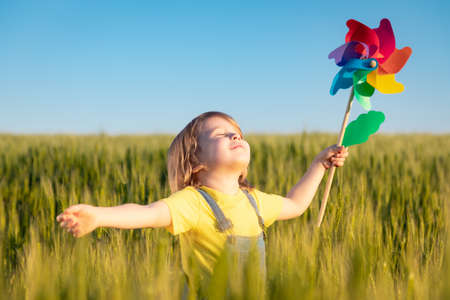Happy child enjoying the sun outdoor in green field. Portrait of kid against summer blue sky background. Freedom and children's dream concept 스톡 콘텐츠
