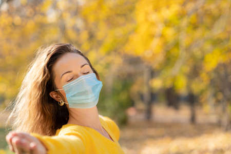 Happy woman wearing protective mask outdoor. Girl having fun in  in autumn park. Freedom and pandemic  concept 스톡 콘텐츠
