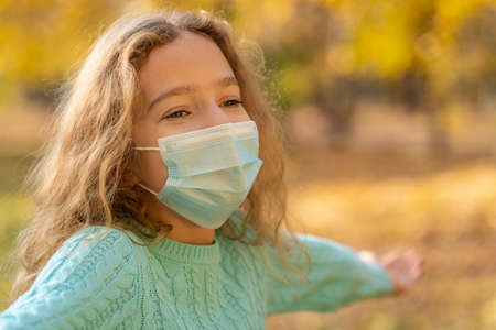 Happy child wearing protective mask outdoor. Girl having fun in  in autumn park. Freedom and pandemic