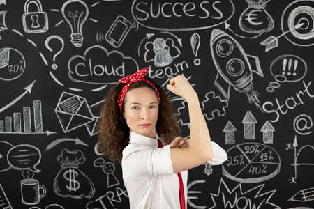 Successful young businesswoman in the office. Woman standing against blackboard. Success business and startup concept
