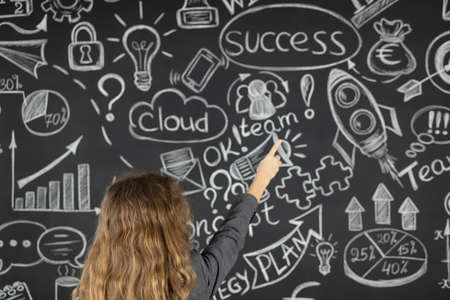 Young businesswoman against chalkboard with business sketch. Success marketing plan and startup concept 스톡 콘텐츠