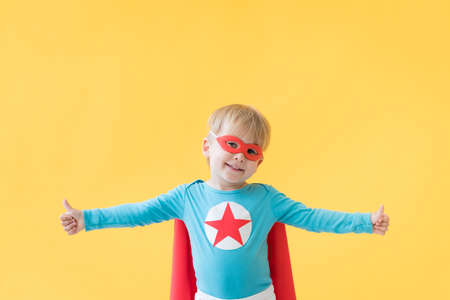 Superhero child against yellow paper background. Super hero kid wearing red mask and cape. Childhood dream and imagination concept