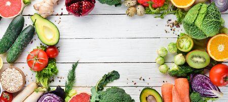 白い木の背景に新鮮な野菜や果物。健康オーガニック食品。トップ ビュー。コピースペースを解放します。 写真素材