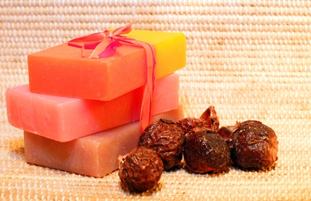 beauty product: Handmade Soap and soap nuts on the bamboo placemat. Spa products Stock Photo