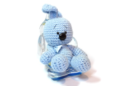 blue knitted hare sitting in the support for mobile telephone photo
