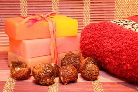 Handmade Soap, soap nuts and red towel on the bamboo placemat. Spa products photo