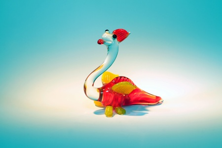 glass figurine of smiling yellow and red dragon in a spotlight on turquoise background photo