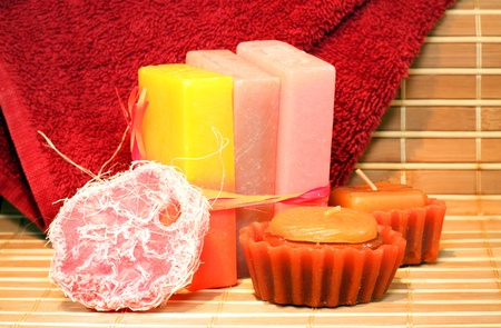 Handmade Soap, chocolate candles and red towel on the bamboo placemate closeup photo