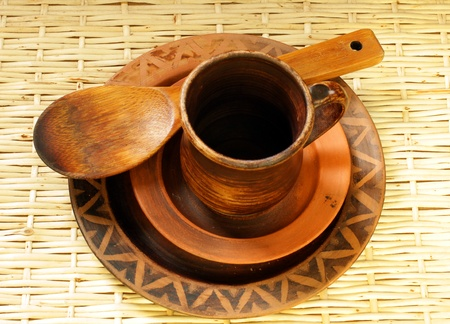 brown clay cup, plates and wooden spoon in ukrainian style handmade photo