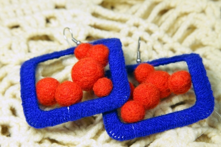 Knitted earrings on the knitted scarf. Handmade. Stock Photo - 17624199