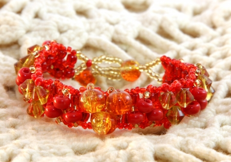 jewelle: Red bracelet handmade from glass on a knitted background