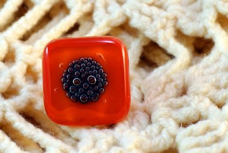origina red glass handmade ring on knitted background photo
