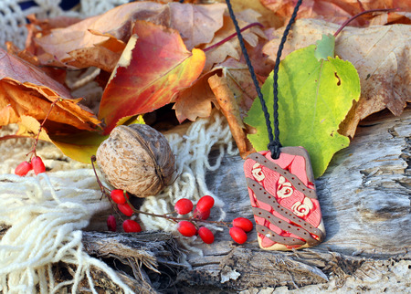 red clay: Ethnic handmade magic red clay amulet on autumn-style background