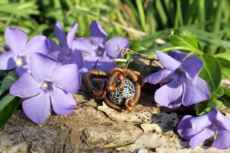 frippery: Handmade bronze ring with wood violet in spring on the nature background