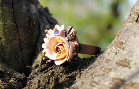 a Hand made ring in a shape of flowers from polymer clay on wooden background