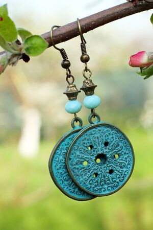 Handmade metal earrings on the nature background ethnic style