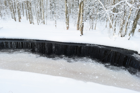 thawed: White snow coast forest river on a background of the dark water of the river thawed Stock Photo