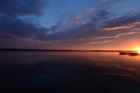 Brightly red halo of sunset near the surface of the water under a blue sky