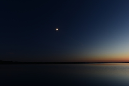 Darkness and light from moonlight in the dark night sky above the lake Stock Photo