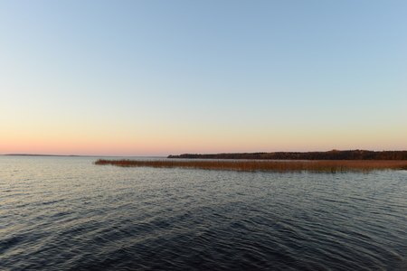 Blue sky with bright colors of sunset afterglow on a forest lake on an autumn evening 版權商用圖片