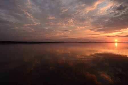 Bright colors of the sky at sunset in the silence of a summer evening reflected on the lake water