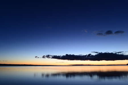Dark color cloud in the blue night sky above the calm water Banque d'images