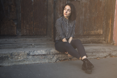 Beautiful young attractive caucasian white brunette fashioned girl dressed in striped shirt sitting behind city wall  background in a old trendy town   . Looking peacefully seductive aside . Stock Photo
