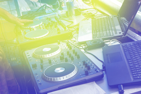 Yellow  tint , blue lines crazy atmospheric straboscope , Beautiful photo of black dj controller with hands dj , setup with stand laptop ,fader crossfader at event party. Stock Photo
